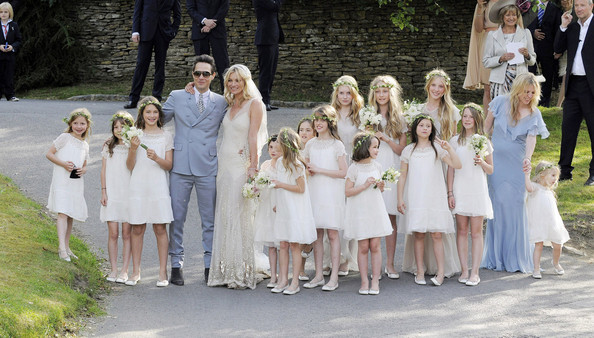 Newly married couple Kate Moss and Jamie Hince smile for photographers immediately after their wedding ceremony held at Southrop Village.