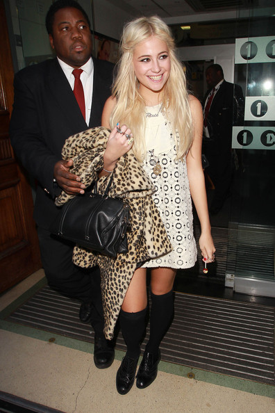 Pixie Lott wears a short white dress and black knee high socks as she leaves Radio 1 Studios. Lott flashed a smile as she held onto an animal print jacket and lollipop.