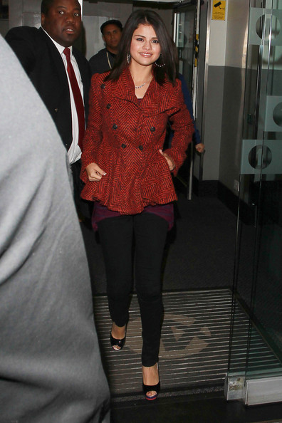 Selena Gomez signs autographs for fans after promoting her new album 'A Year Without Rain' at Radio 1 studios in London. Selena could be seen wearing a red tweed jacket, large hoop earrings and black high heels as she emerged from the London studios.