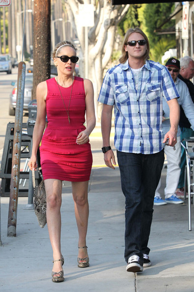 Sharon Stone The classy Sharon Stone is seen wearing a short red dress while out and about with a friend in Los Angeles.  Stone, 53, sports dark sunglasses, with a snake skin purse and matching heels.