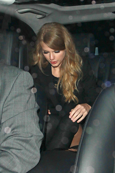 Taylor Swift Taylor Swift leaves a London hotel where she spent the whole day at a photoshoot for GQ Magazine. The leggy country singer stayed stylish in a black blazer over a lacy black dress worn with knee high socks. Swift is scheduled to perform live at the 44th CMA Awards show in Nashville.