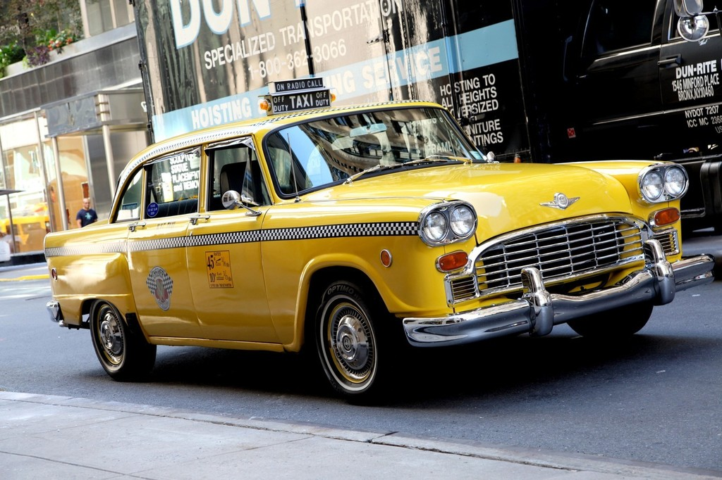 a vintage yellow new york taxi cab is seen driving in. Black Bedroom Furniture Sets. Home Design Ideas